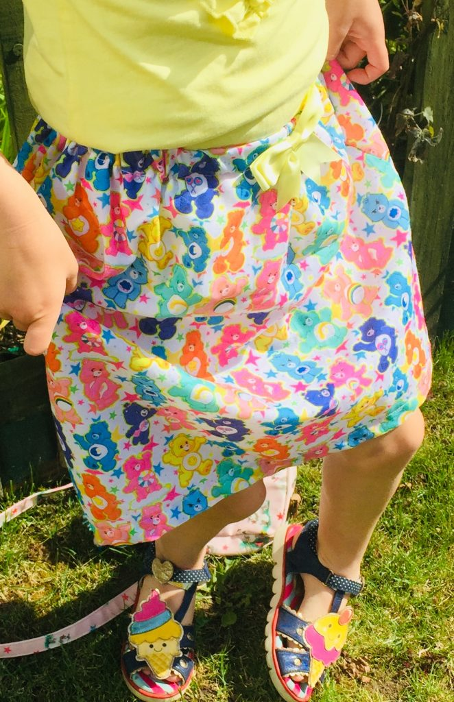 Elasticated Skirt 6-7 years in Polly cotton fabric, with Carebear design & 8mm green bow