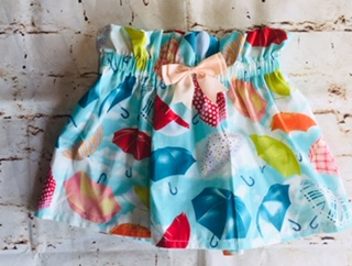 High Waisted Elasticated Skirt (3-4 years) in Light blue cotton fabric with different coloured umbrellas design, with a 8cm peach bow