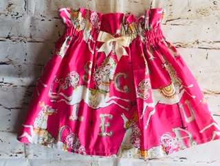 High Waisted Elasticated Skirt (3-4 years) in Pink cotton fabric with merry go round horse design , with a 8cm cream bow