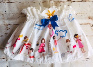 High Waisted Elasticated Skirt (3 years) in White cotton fabric with sketched children design, with a 8cm blue bow