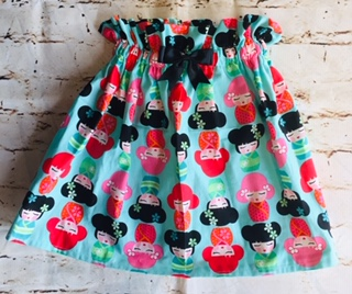 High Waisted Elasticated Skirt (5-6 years) in Mint green cotton fabric with china doll design , with a 8cm black bow